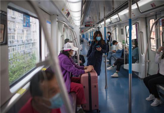 4月16日,武汉市民保持距离乘坐轨道交通一号线列车。新华社记者 肖艺九 摄