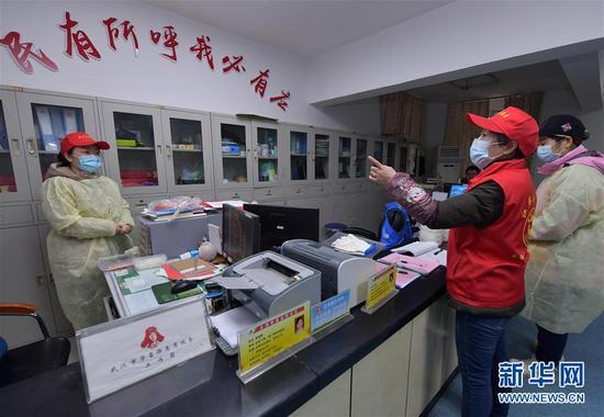 武汉市永清街道沈阳社区干部(右二)在社区办公室为同事分配工作任务(2月12日摄)。 新华社记者 李贺 摄