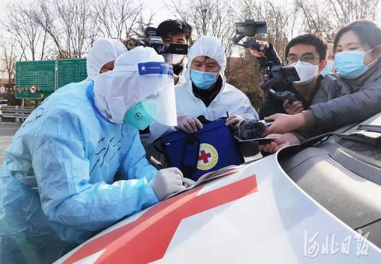 石家庄裕华路高速口,石家庄市红十字会工作人员正在与北京市红十字会紧急救援中心(999)工作人员(左一)进行交接。河北日报记者赵海江摄