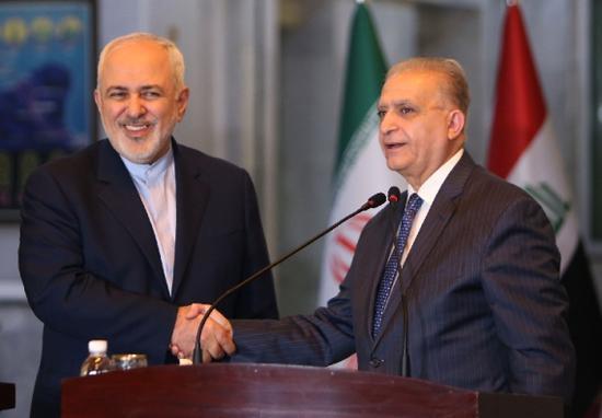 1月13日,在伊拉克巴格达,伊拉克外长哈基姆(右)与伊朗外长扎里夫在联合新闻发布会后握手。(新华/法新)