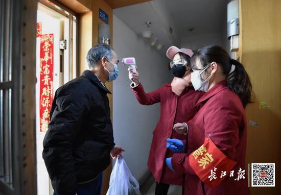 2月17日,江汉区花楼社区,工作人员逐户排查、为居民测量体温并送来菜品