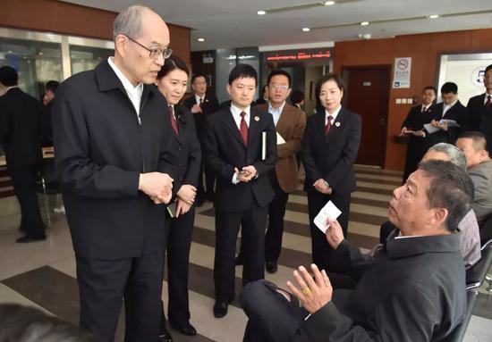 在检察服务大厅,张军检察长与前来办理事务的群众交流,了解群众诉求。