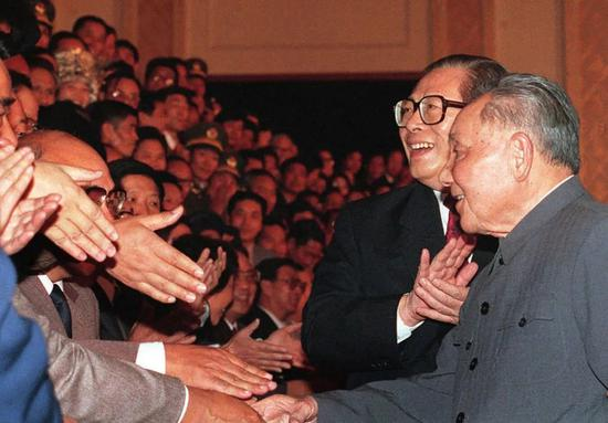 1992年10月19日,在北京人民大会堂,邓小平在江泽民的陪同下,绕场一周,和代表们见面。1992年10月12日至18日,中国共产党举行第十四次全国代表大会。大会明确提出了中国经济体制改革的目标是建立社会主义市场经济体制。图/新华