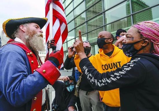 ·当地时间5日,密歇根州一计票中心外双方撑持者发作争论。