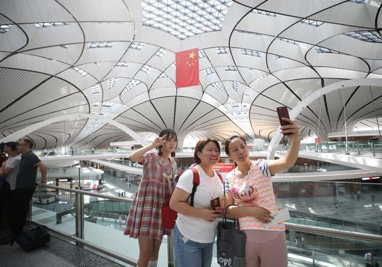 北京大兴机场旅客自拍留念。(中国日报记者 陈泽冰 摄)