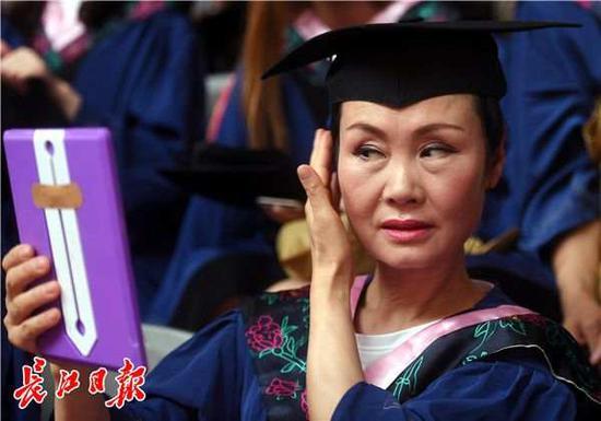 参加毕业典礼的周亚松在整理妆容