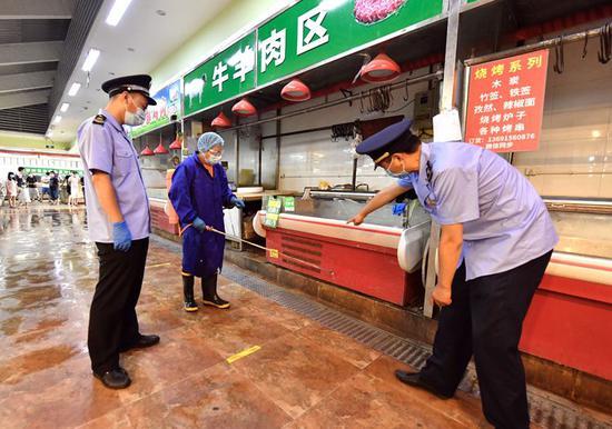 特吉特菜市场,东城市场监管局执法人员检查摊位消毒情况。