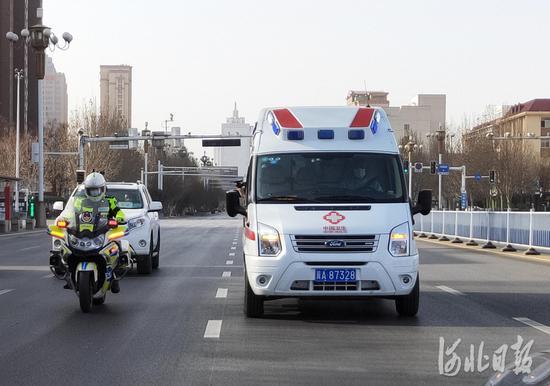 """1月11日14时左右,载着""""生命种子""""的救护车在交警的护送下前往石家庄市裕华路高速口。河北日报记者赵海江摄"""
