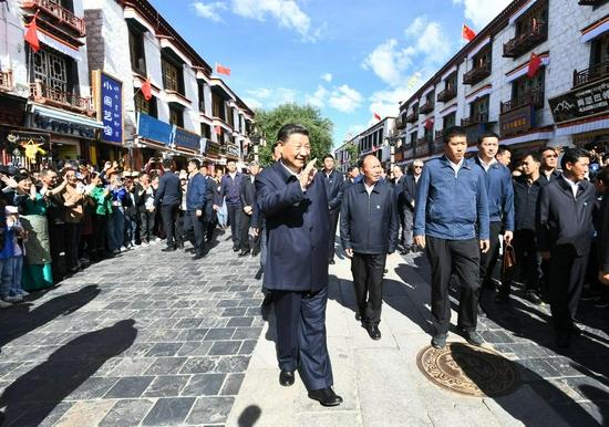 7月22日下午,习近平在考察位于拉萨市老城区的八廓街时,向各族群众挥手致意。新华社记者 谢环驰 摄