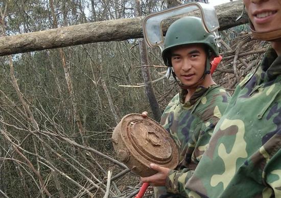 杜富国(左)排除了1枚反坦克地雷。杨萌 摄