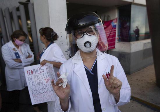 (医护人员手持标语,现身街头。图源:美联社)