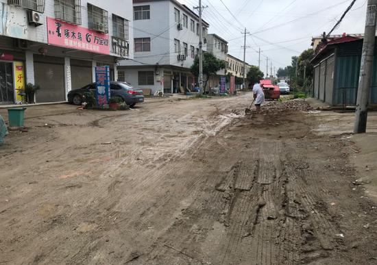 6月12日上午,因为刚下过大雨,一位八四集居民在填后街的泥泞路面。新京报记者 肖隆平 摄