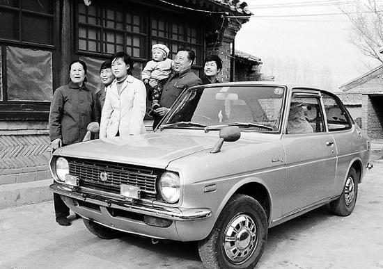 """1984年,""""养鸡状元""""孙桂英(左一)家购入了一辆丰田小轿车。图为她和家人在车旁留影。李晞/摄"""