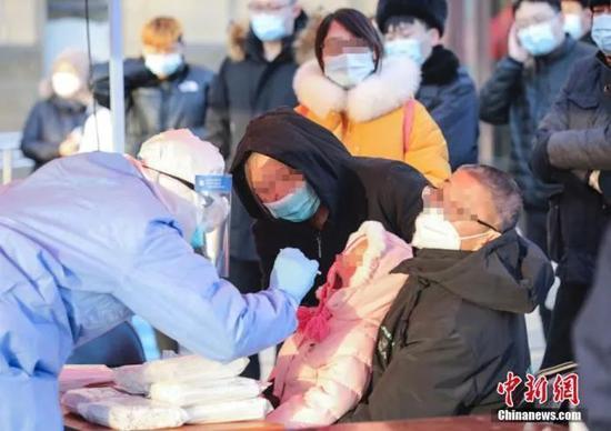 资料图:北京大兴区高米店街道的一处采样点,工作人员对居民进行核酸检测采样。中新社记者 赵隽 摄