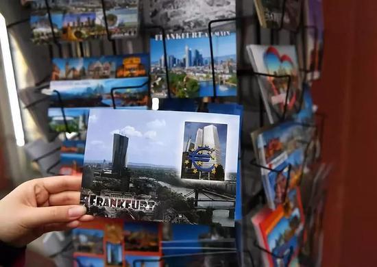 这是2018年12月30日在德国法兰克福拍摄的印有欧元塔和欧元雕塑图案的明信片。新华社记者逯阳摄