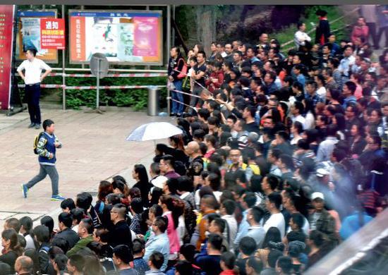 """2016年4月, """"全国小学数学奥林匹克比赛""""决赛在四川成都的一个考点,家长等待学生出来。图/视觉中国"""