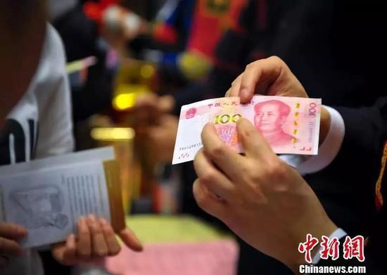 资料图:银行志愿者讲解如何辨别新版人民币的真伪。 刘新 摄
