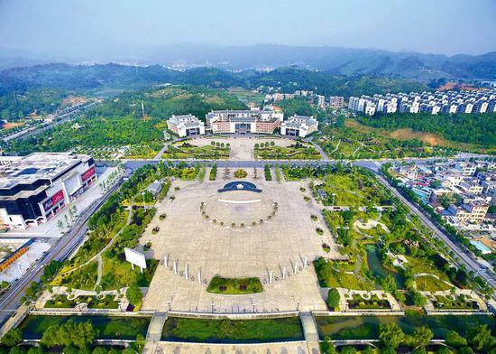 湖南省汝城县举债修建的爱莲广场,仅6棵银杏树就花了285万元,8根图腾石柱花了120万元。与广场相对的是县委县政府的办公大楼。图/《中国纪检监察报》