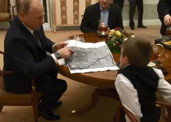 普京拿出地图,向男孩介绍航线。