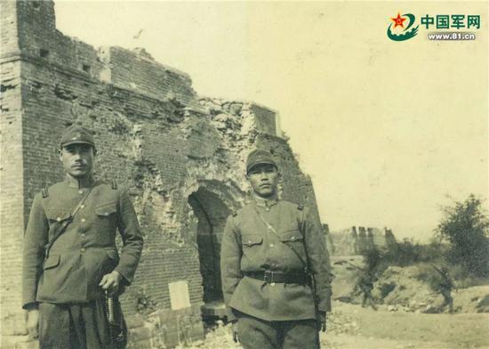 德田(左)在遭日军炮击后残破的宛平城东门(顺治门)前留影。