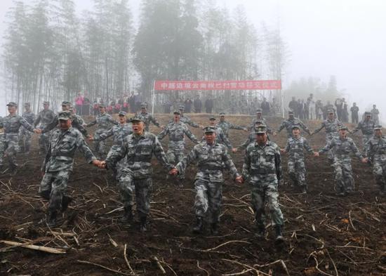 南部战区陆军云南扫雷大队官兵在云南省麻栗坡县老山西侧坝子雷场手拉着手徒步验收已扫雷场。彭希  摄