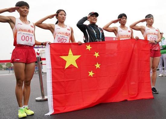 10月23日,中国队成员在女子个人全能越野跑比赛后手持国旗敬礼。