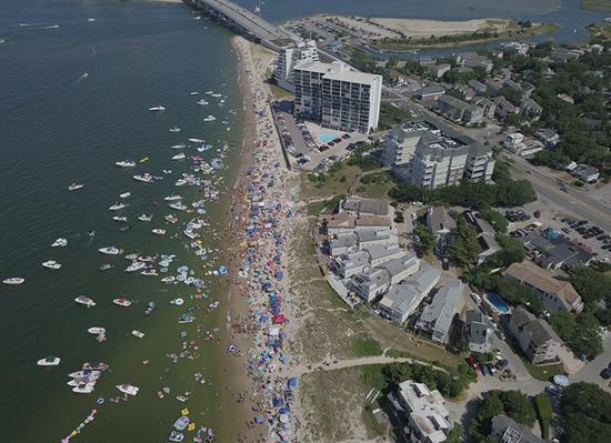 庆祝狂欢节的人们将成堆的垃圾扔在海滩上