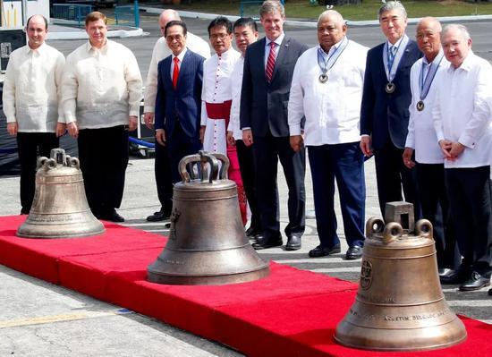 2018年12月11日,在菲律宾马尼拉维拉摩尔空军基地,菲律宾国防部长洛伦扎纳(右二)出席三口古钟交接仪式。新华社/美联