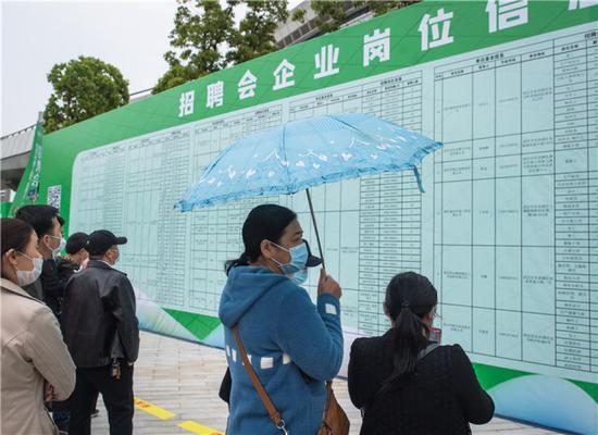 4月21日,求职者在武汉市复工复产企业用工现场招聘会上查看招聘信息。新华社记者 肖艺九 摄