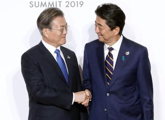 6月28日,日本首相安倍晋三迎接韩国总统文在寅抵达会场,两人握手。