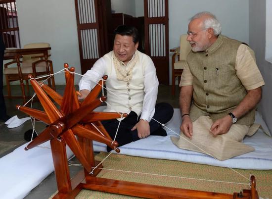 2014年9月17日,国家主席习近平在印度古吉拉特邦进行访问。印度总理莫迪全程陪同。这是习近平在参观甘地故居时,亲自摇动甘地曾经使用过的纺车。新华社记者马占成摄