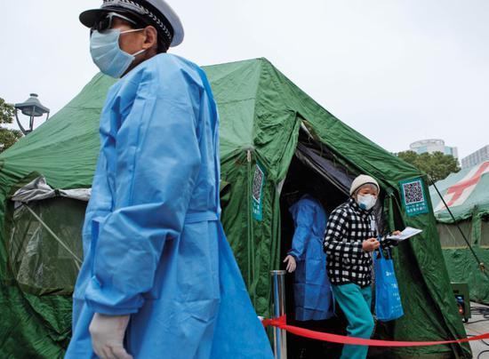 2月3日,上海长海医院架设3顶军队野战帐篷作为入院通道,患者在此初检、测体温、登记健康信息。摄影/雍和