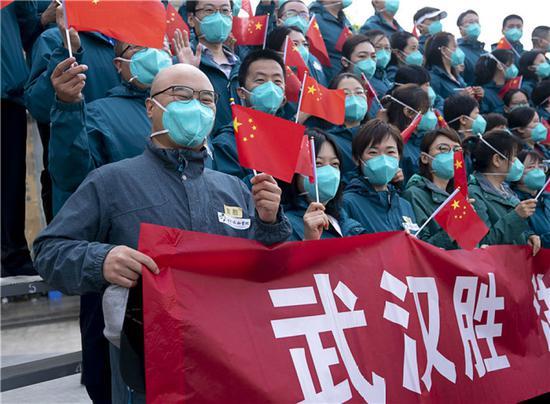 4月15日,北京协和医院国家援鄂抗疫医疗队队员挥舞国旗。当日,北京协和医院国家援鄂抗疫医疗队约180人启程回京。新华社记者 熊琦 摄