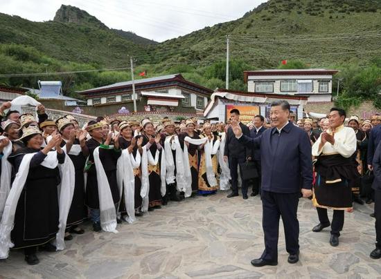 7月21日下午,习近平在林芝市巴宜区林芝镇嘎拉村考察时,向村民们挥手致意。新华社记者 李学仁 摄