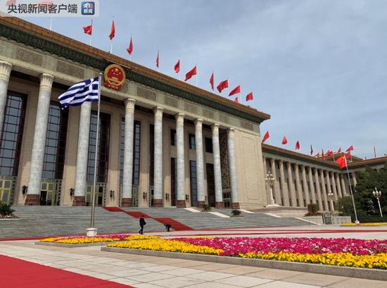 △希腊国旗在人民大会堂东门外广场升起,欢迎希腊总统的仪式即将开始。(央视记者段德文拍摄)