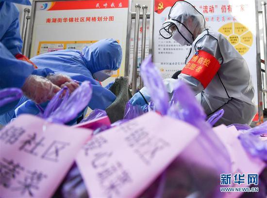 武汉市武昌区华锦社区的志愿者为社区居民分装爱心蔬菜(2月23日摄)。 新华社记者 程敏 摄