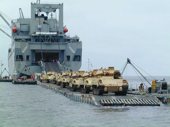 资料图片:美海军大型运输舰借助浮桥向滩头运送M2步兵战车群。(图片来源于网络)