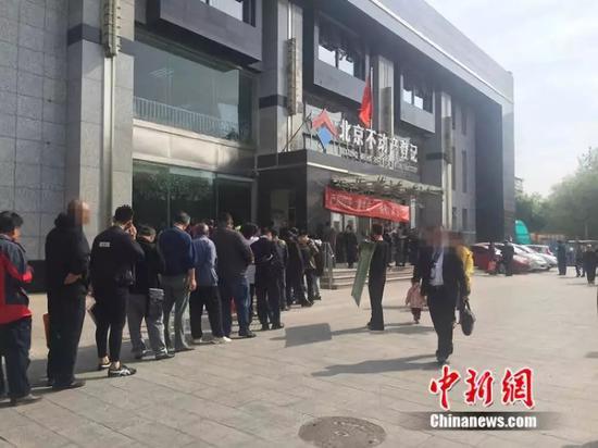 资料图:2016年4月,北京丰台区不动产登记事务中心外排起长队。中新网 邱宇 摄