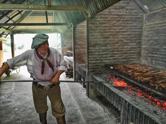 在布宜诺斯艾利斯市郊的圣•苏珊娜农场,男主人在为客人制作传统阿根廷烤肉。(新华社记者王晔摄)