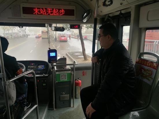 """郑州市一辆44路公交车上挨近司机的乘客座位,被贴上了一张""""吾是公交坦然守护员""""的贴纸。受访者供图"""