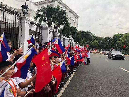 △来自当地三所小学的千名小学生站在总统府道路两侧挥舞两国国旗,欢迎习近平车队