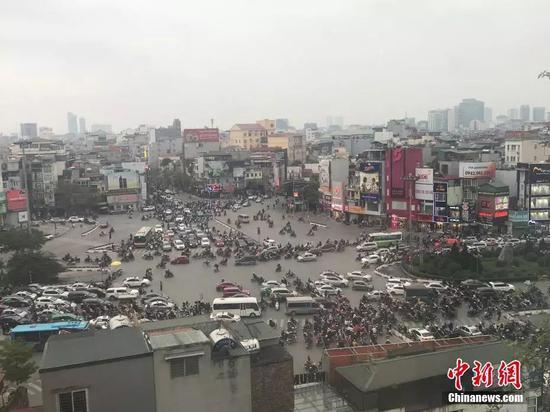 2月25日,越南首都河内,第二次朝美领导人会晤举行前,河内街头民众正常出行,摩托为当地主要出行方式之一。正值下班高峰期,大量摩托车在路口准备过路。中新网记者孟湘君 摄