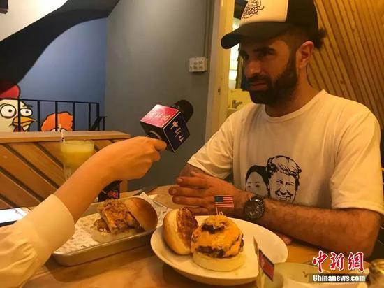 当地时间2月25日,河内市中心一家餐厅推出两款以金正恩、特朗普为主题的汉堡,招徕顾客。图为汉堡设计者之一接受中新社、中新网采访。中新网记者孟湘君 摄
