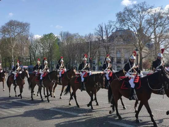 △在100多名法兰西共和国卫队骑兵和摩托车队的护卫下,两国元首乘车前往爱丽舍宫。(央视记者耿小龙拍摄)