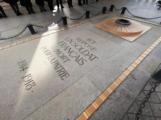 """△凯旋门下的无名烈士墓。法国议会1919年以隆重安葬一名无名烈士的方式悼念150万名在一战中阵亡的法国官兵。无名烈士墓建于1920年11月11日(一战停战两周年纪念日),其上铭刻""""这里安息着一名为国捐躯的法国士兵"""",并从1923年11月11日起点燃长明火。(央视记者张晓鹏拍摄)"""