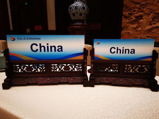 △圓桌峰會桌簽的設計靈感來源于中式雕花屏風設計。為了讓畫面構圖達到最佳效果,習主席桌上的桌簽是精心挑選過尺寸的。這是在早前的論壇演練中《時政新聞眼》拍到的。(央視記者張曉鵬拍攝)