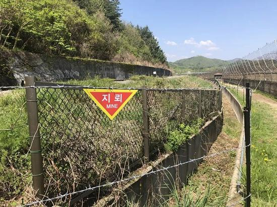 """铁丝网上悬挂着的""""地雷""""警示牌。新华社记者陆睿摄"""