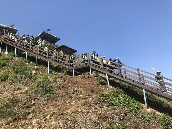 """身着青绿色背心的游客在导游带领?#38470;?#20837;""""非军事区和平之路""""步道。新华社记者陆睿摄"""