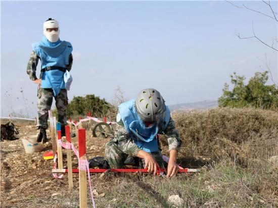 """中国维和官兵扫雷作业手在位于黎巴嫩南部靠近以色列边境的""""蓝线""""附近作业(2017年11月8日摄)。新华社发(董永康 摄)"""