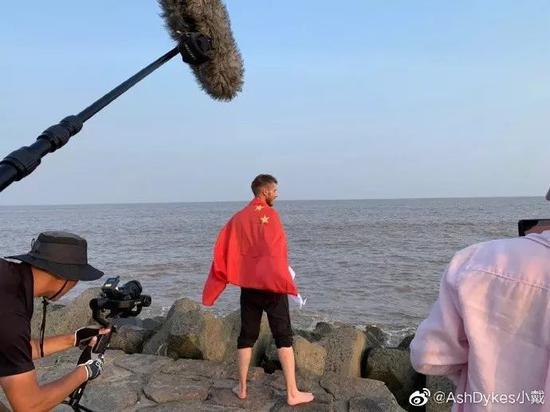 ▲小戴身披中国国旗站在长江入海口。(小戴微博截图)
